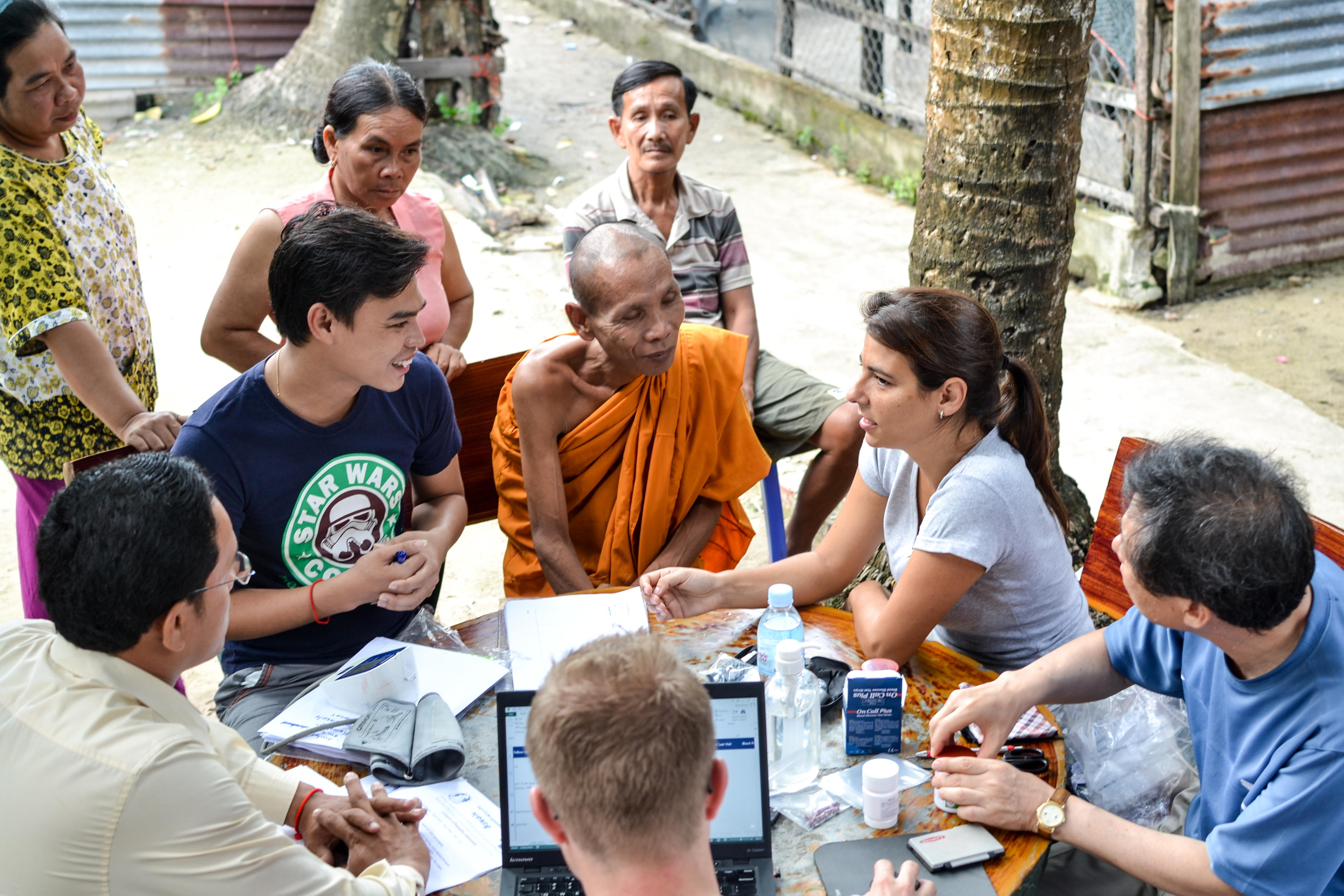 An intern is seen talking to locals during an outreach whilst she completes her public health internship in Cambodia with Projects Abroad.